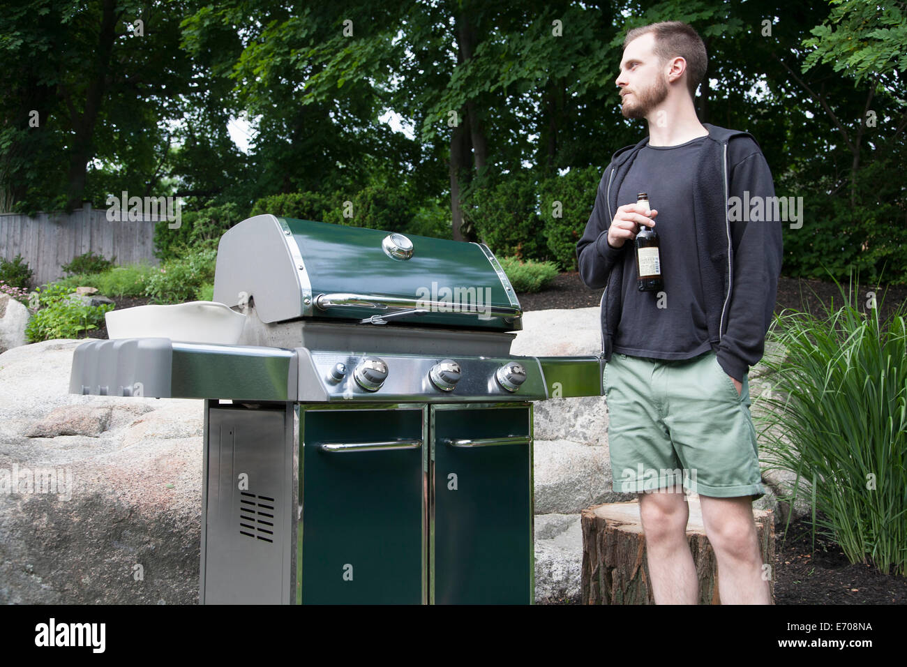 Mid adult man standing by barbecue with bottle of beer in garden - Stock Image