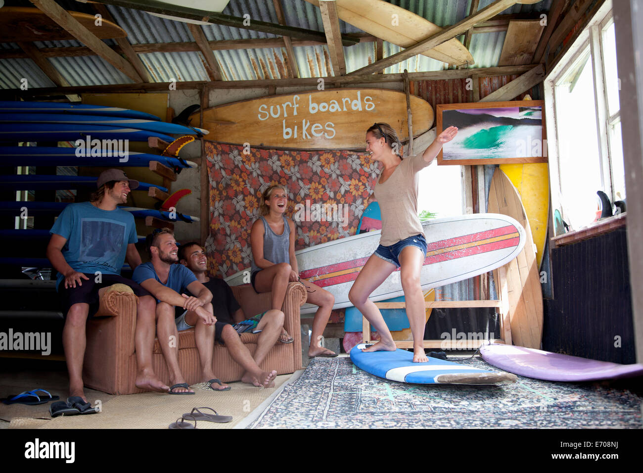 Five young adult surfer friends fooling around in surf shed - Stock Image