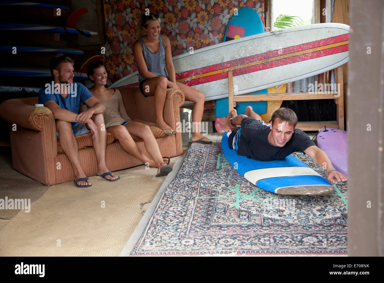 Four young adult surfer friends messing around in surf shed - Stock Image