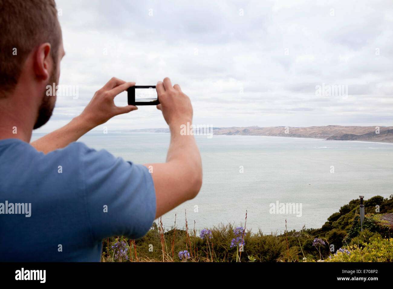 Rear cropped view of young man photographing sea with smartphone - Stock Image