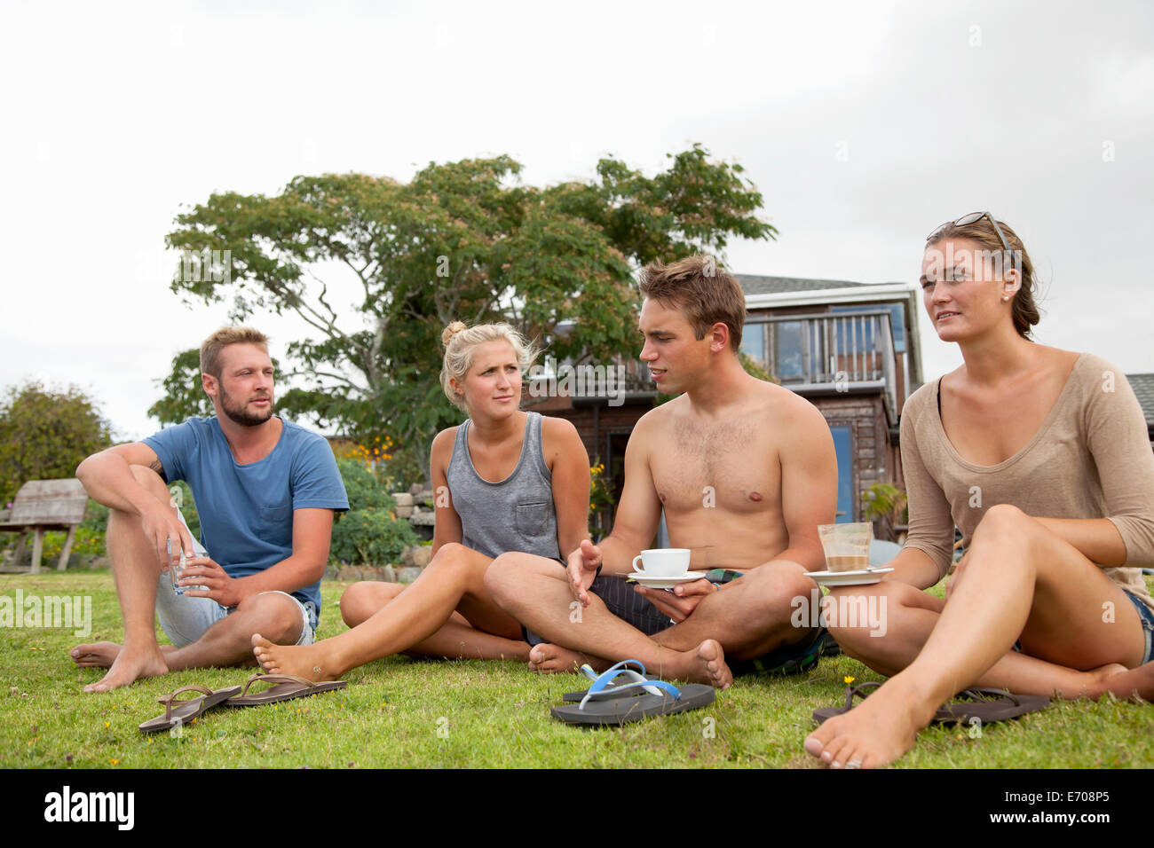 Four friends sitting outside hostel chatting and drinking coffee - Stock Image