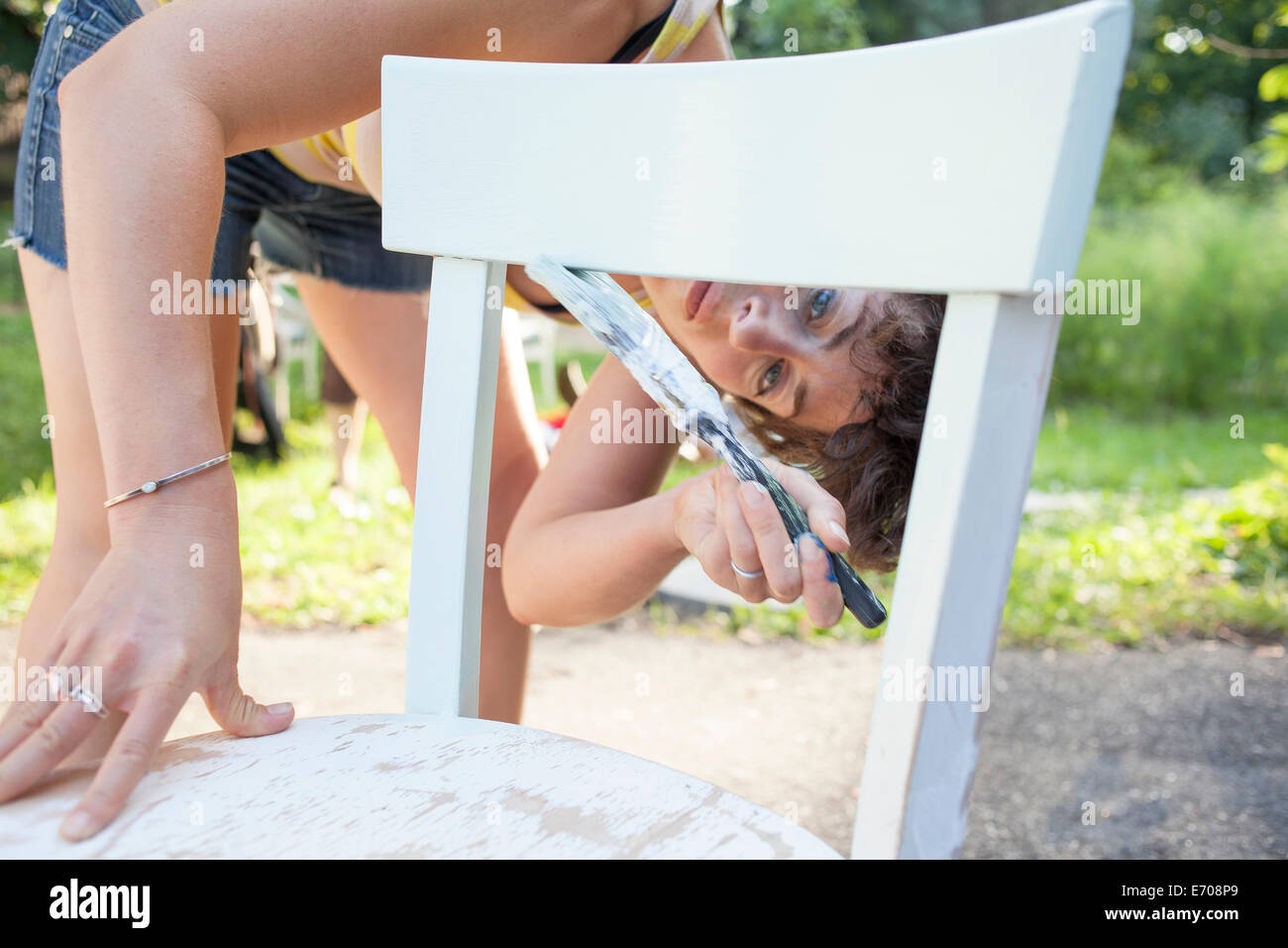 Mid adult woman bending forward to paint and restore chair in garden - Stock Image