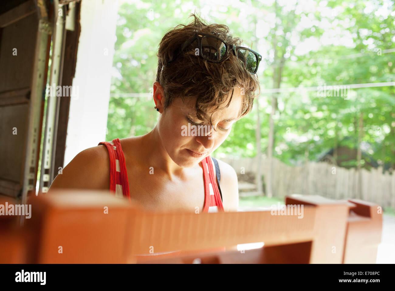 Mid adult woman restoring furniture in garage - Stock Image