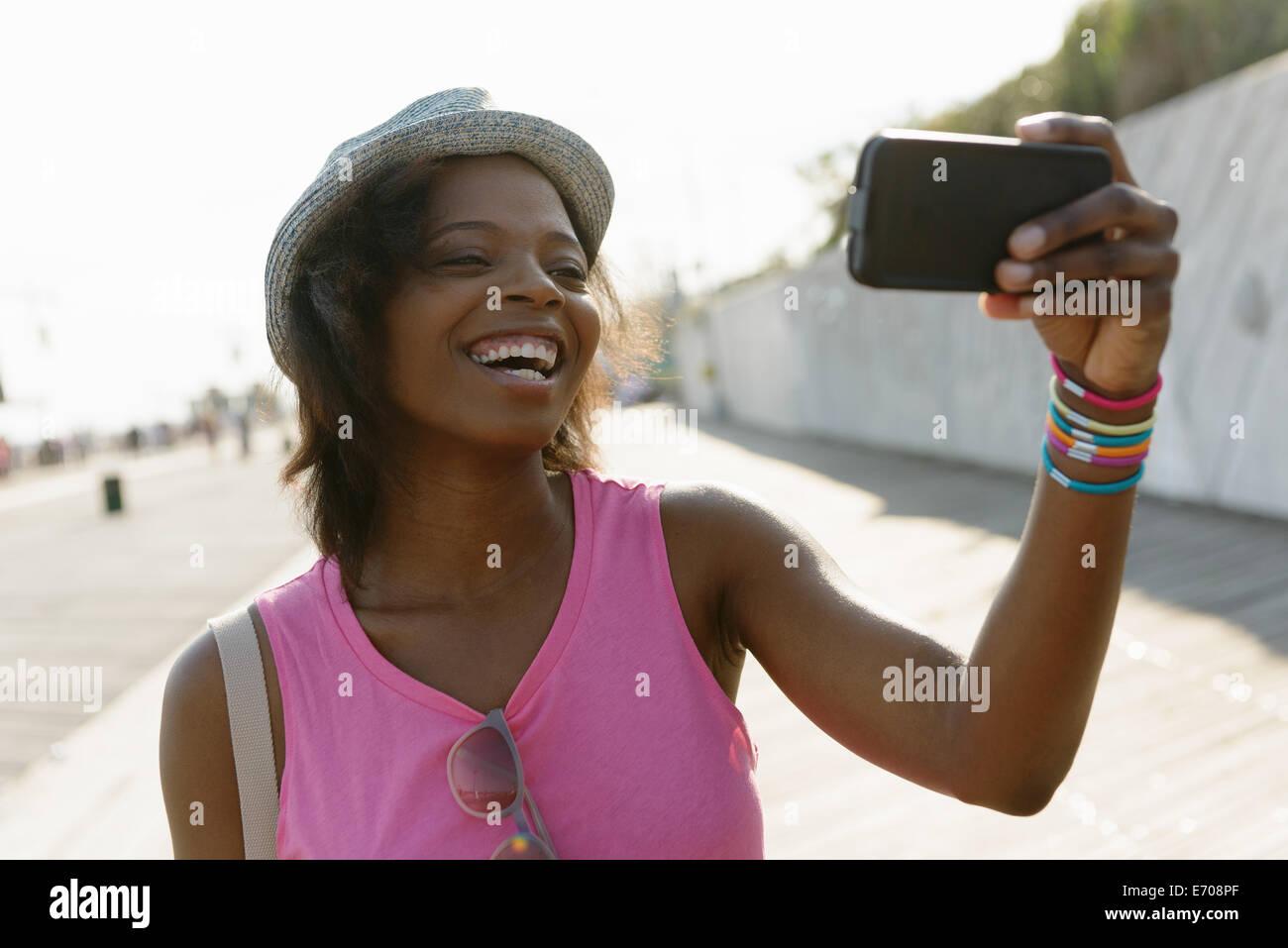 Young woman taking selfie on smartphone, Coney Island, Brooklyn, New York, USA Stock Photo