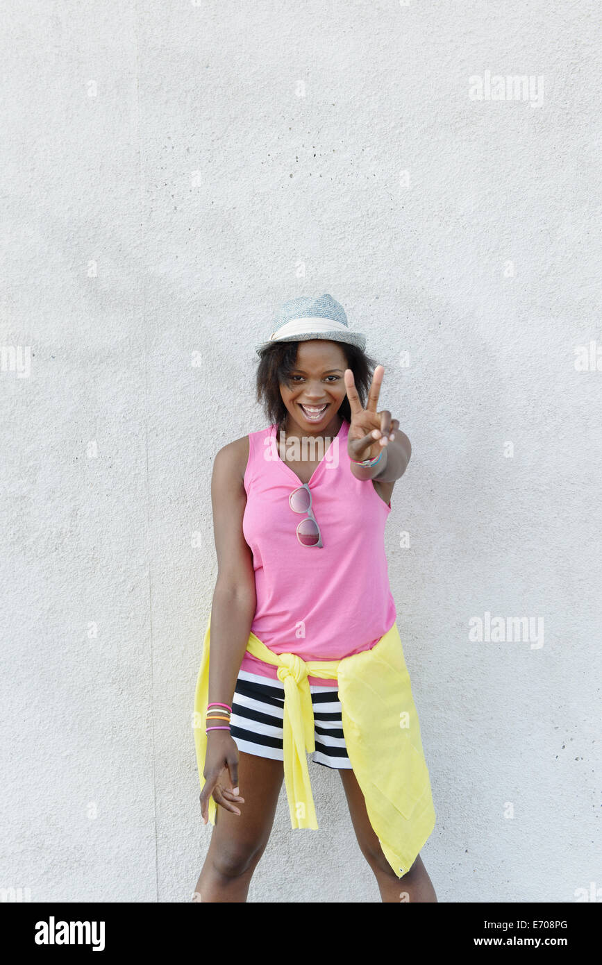 Portrait of young woman making peace sign in front of wall, Coney Island, Brooklyn, New York, USA - Stock Image