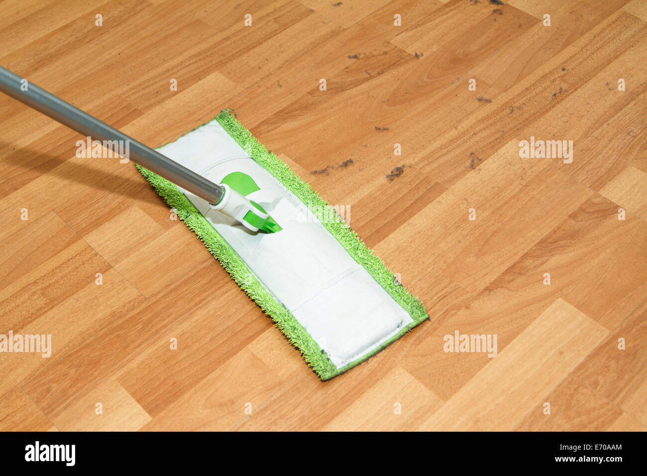 Mop cleaning and washing the wooden parquet floor in room. - Stock Image