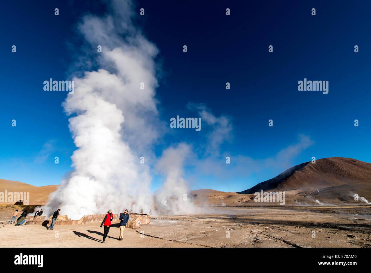 People walking across Tatio Geysers Geothermal fields San Pedro de Atacama Chile South America - Stock Image