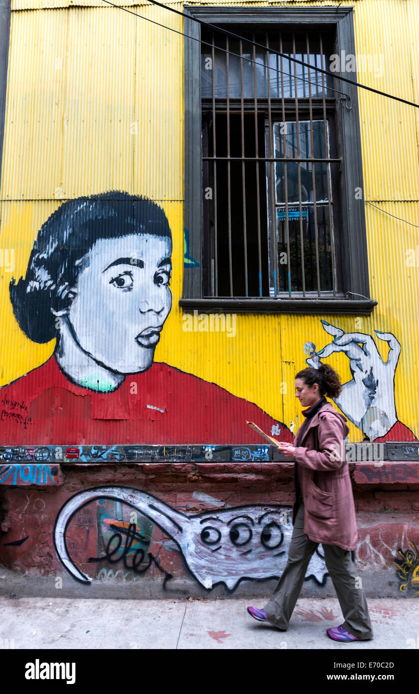 Woman walking by a mural in Valparaiso, Chile, South America - Stock Image