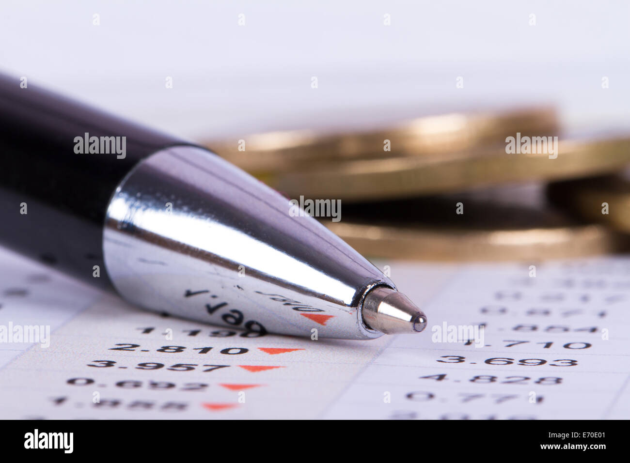 Close up view of pen on financial data analysis and coins behind. - Stock Image