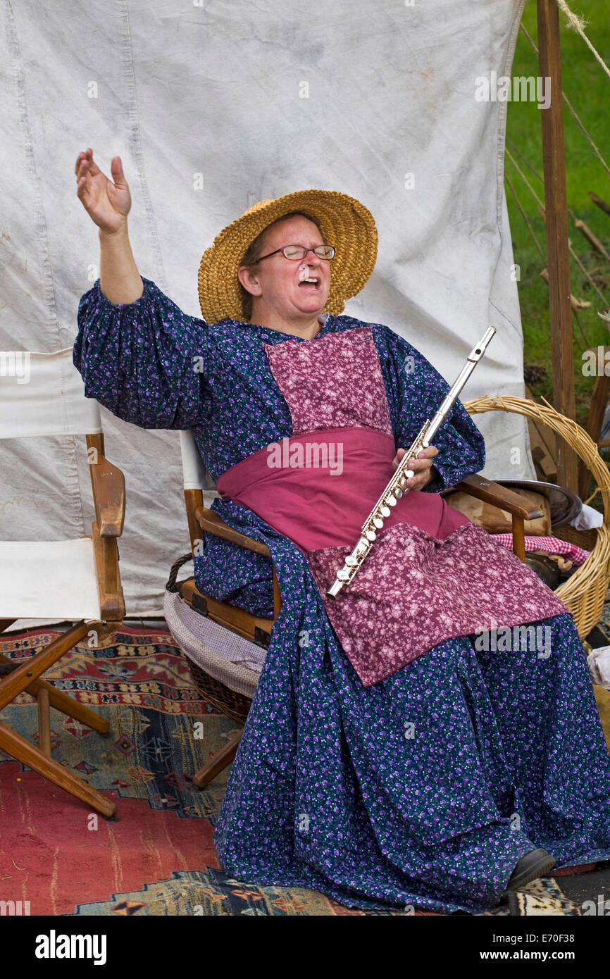 A woman sings a hymn at  a Civil War reenactment between northern and southern soldiers held in the Metolius River - Stock Image