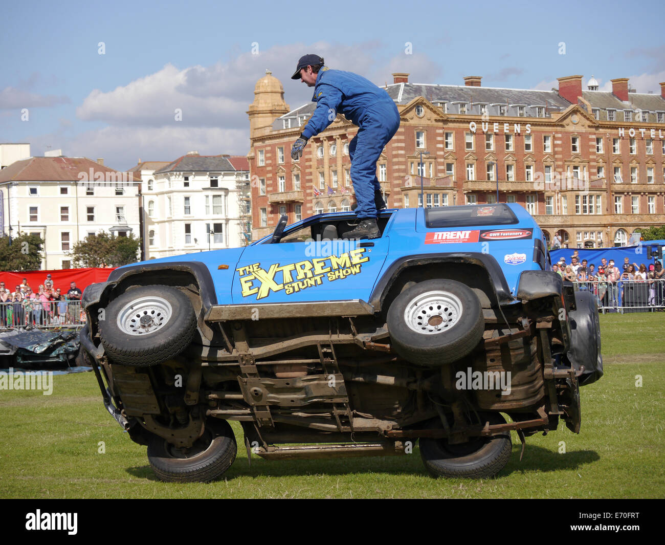 A passenger stands on the outside of a vehicle as it drives on two wheels at the Extreme stunt show in Portsmouth, - Stock Image