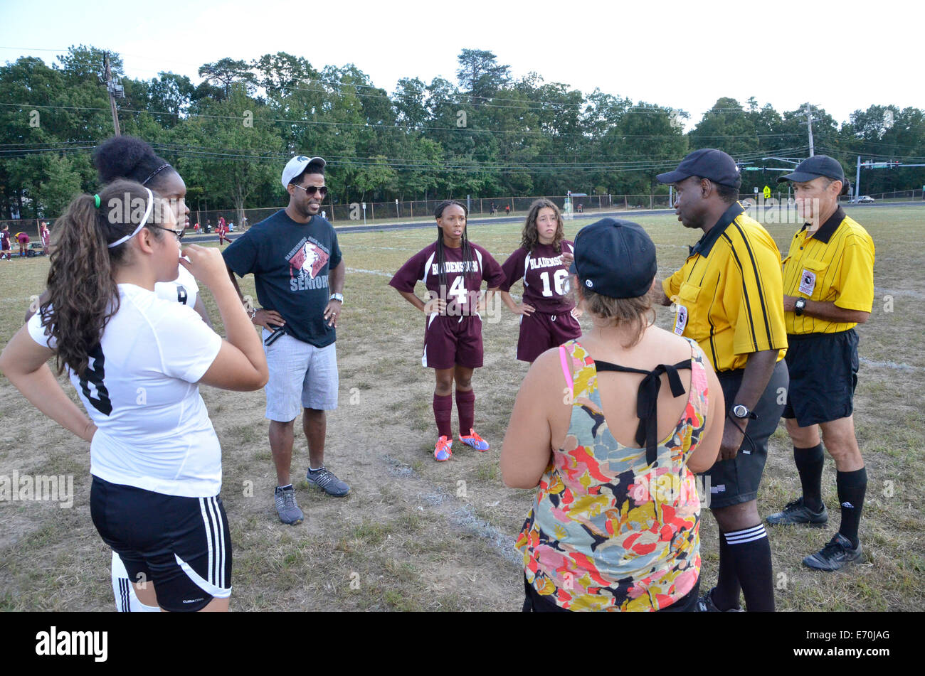 Soccer teams and coaches meet with referees prior to the beginning of a high school soccer game - Stock Image