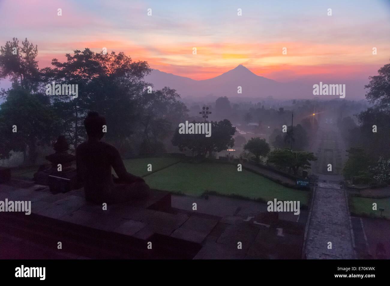 Borobudur, Java, Indonesia.  Buddha Statue and Mount Merapi at Sunrise in Morning Mist. - Stock Image