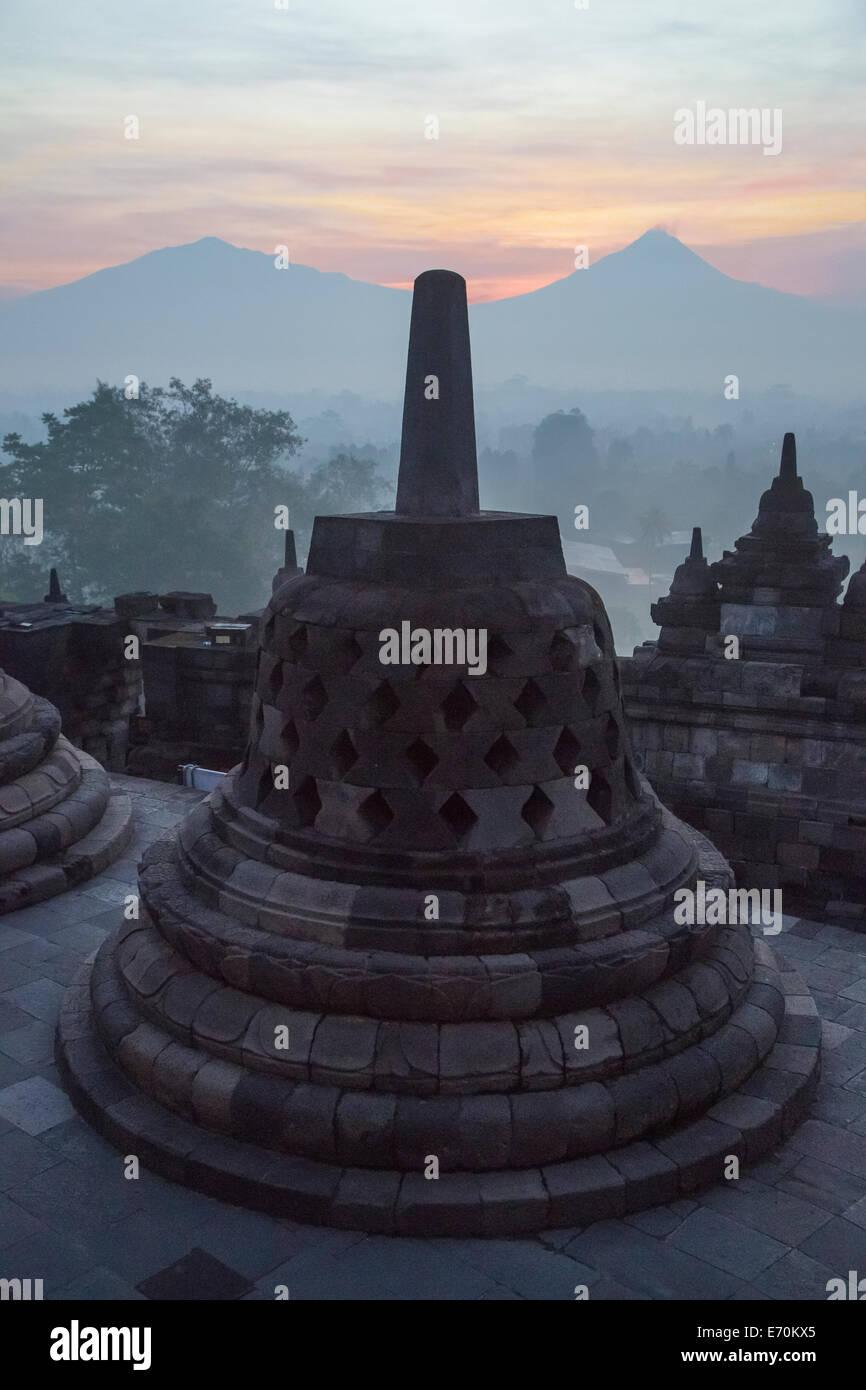 Borobudur, Java, Indonesia.  Stupa and Mount Merapi at Sunrise in Morning Mist. - Stock Image