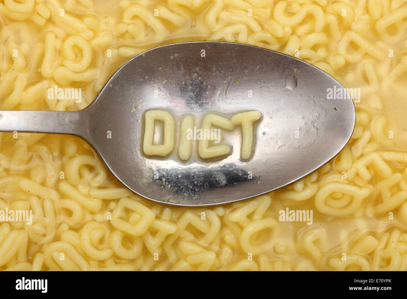 Alphabet letters in spoon spell out 'Diet'. Alphabet Soup Pasta. Closeup. - Stock Image