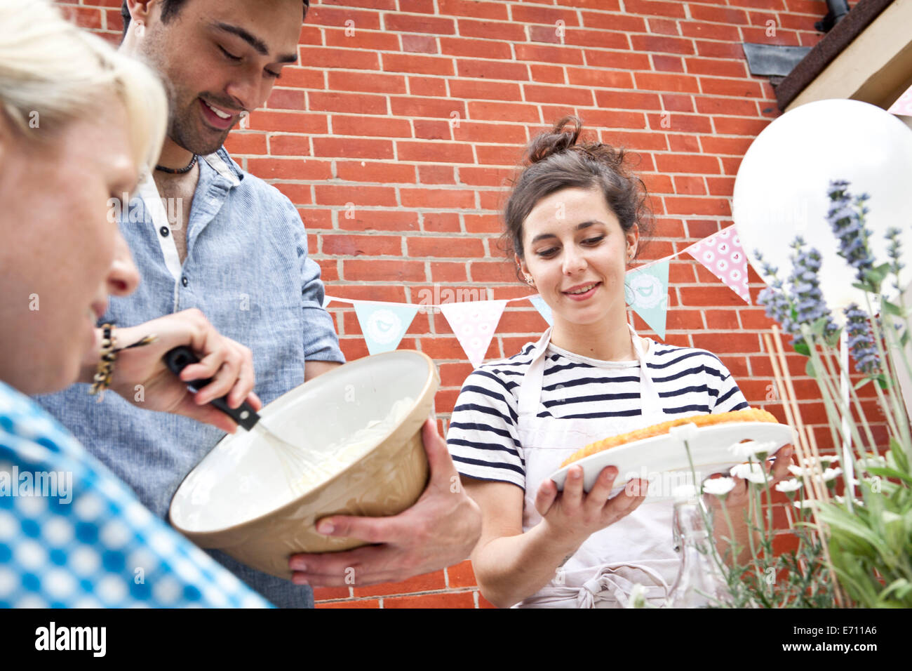 Three friends preparing fruit flan and meringue at garden party - Stock Image