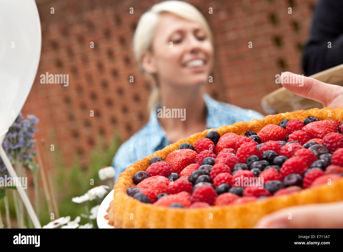 Two female friends with fruit flan at garden party - Stock Image