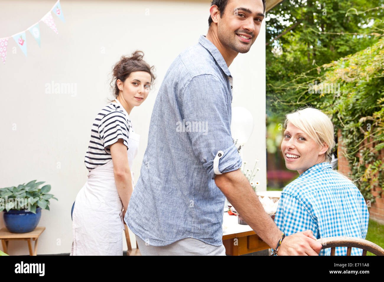Three young adult friends at garden party - Stock Image