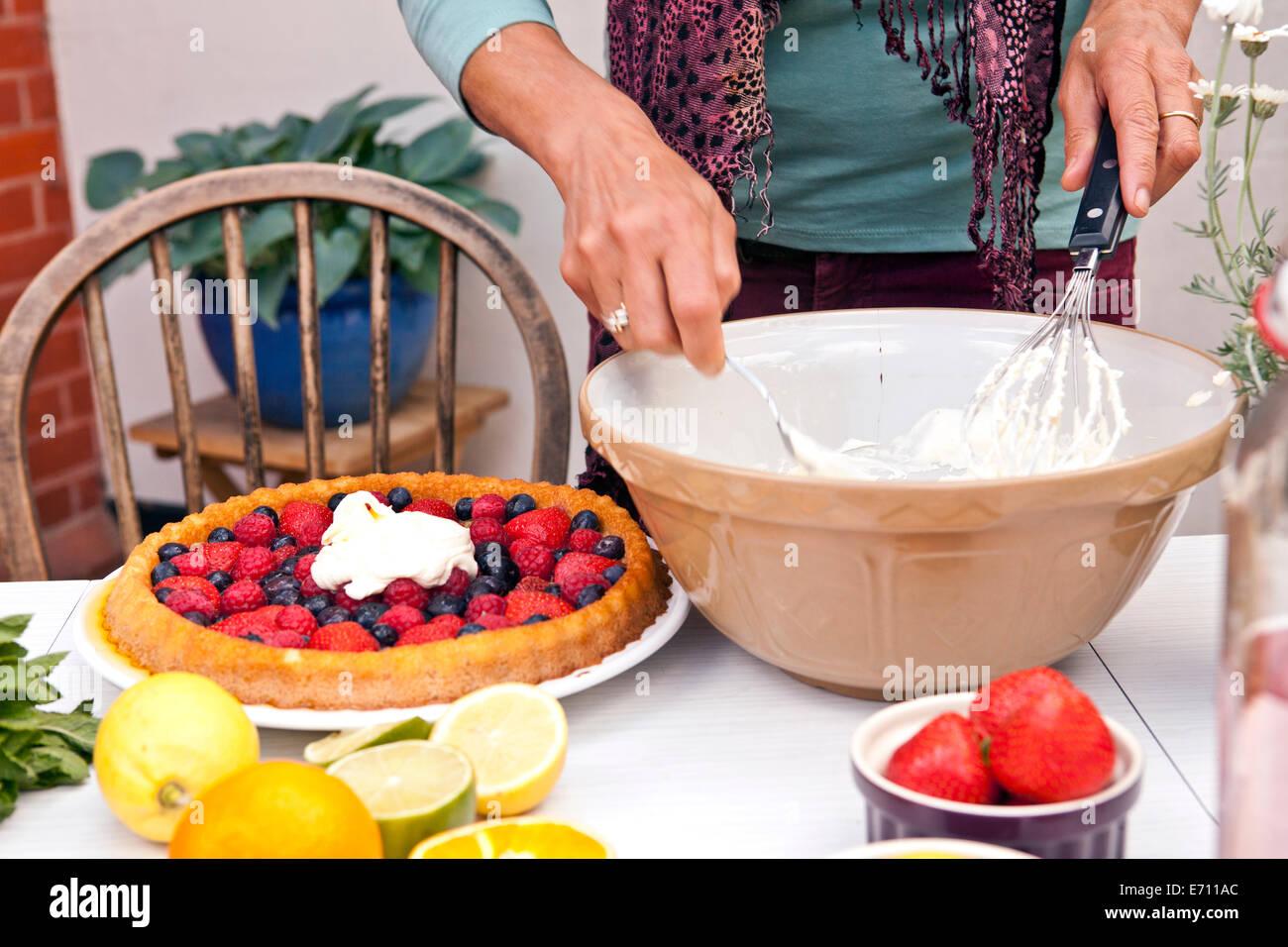 Cropped shot of mature woman preparing fruit flan at garden party - Stock Image