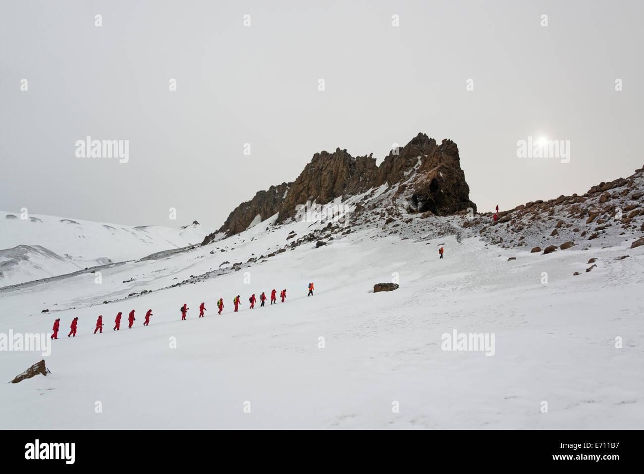 Travellers in bright orange waterproofs walking in a line across the snow on Deception island. - Stock Image