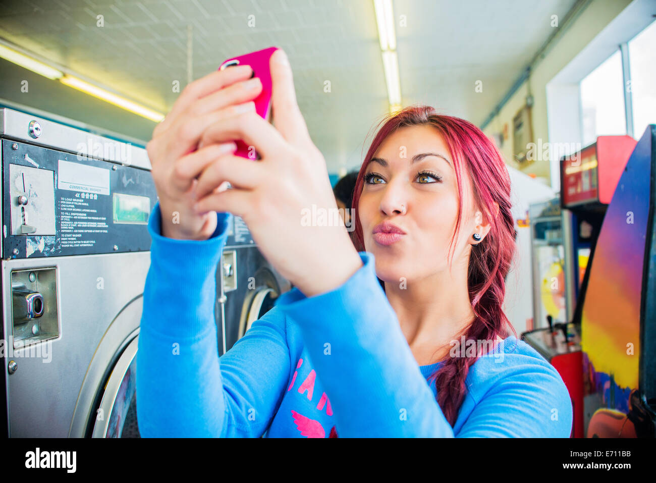 Young woman in laundromat, taking self portrait with smartphone - Stock Image