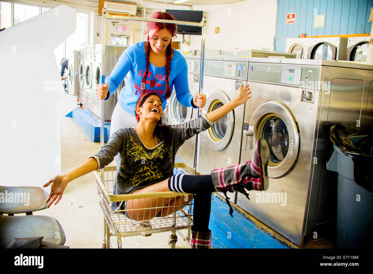 Two young women in laundromat, one pushing the other along in trolley - Stock Image