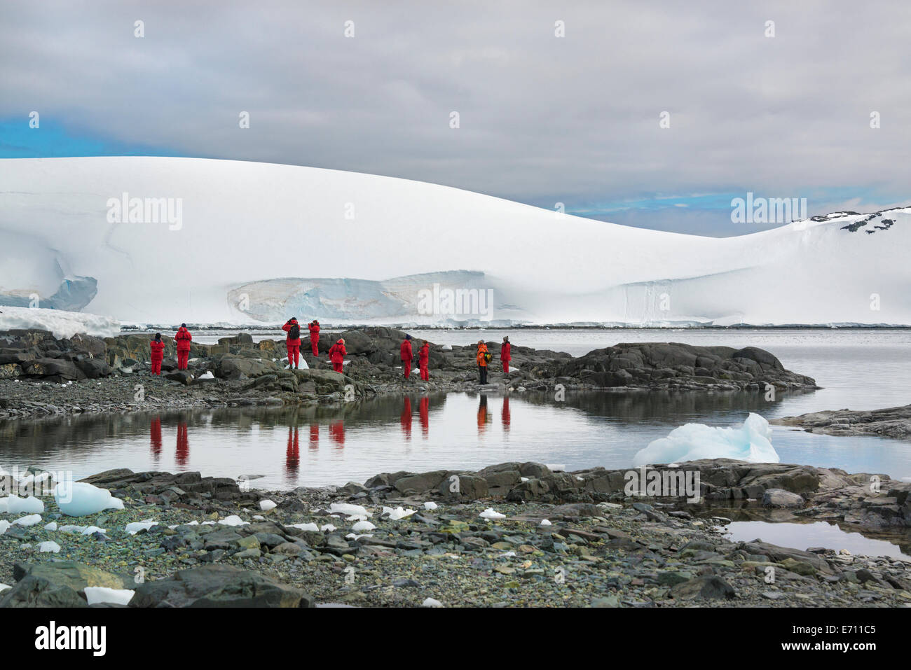 Travellers in bright orange waterproofs observing and photographing the scenery and wildlife on an Antarctic island. - Stock Image