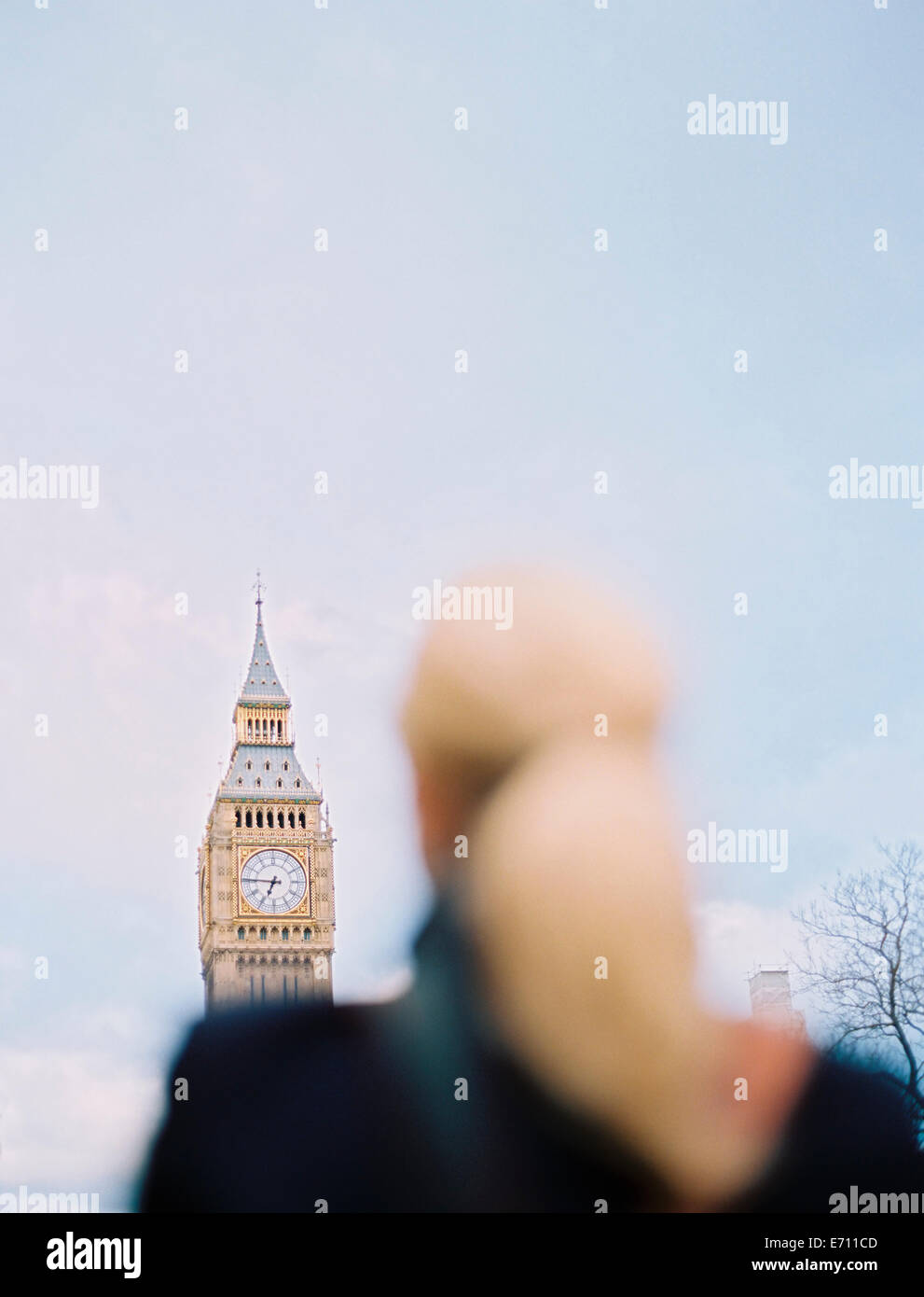 A woman looking up at Big Ben, The Elizabeth Tower at the Houses of Parliament in London. - Stock Image