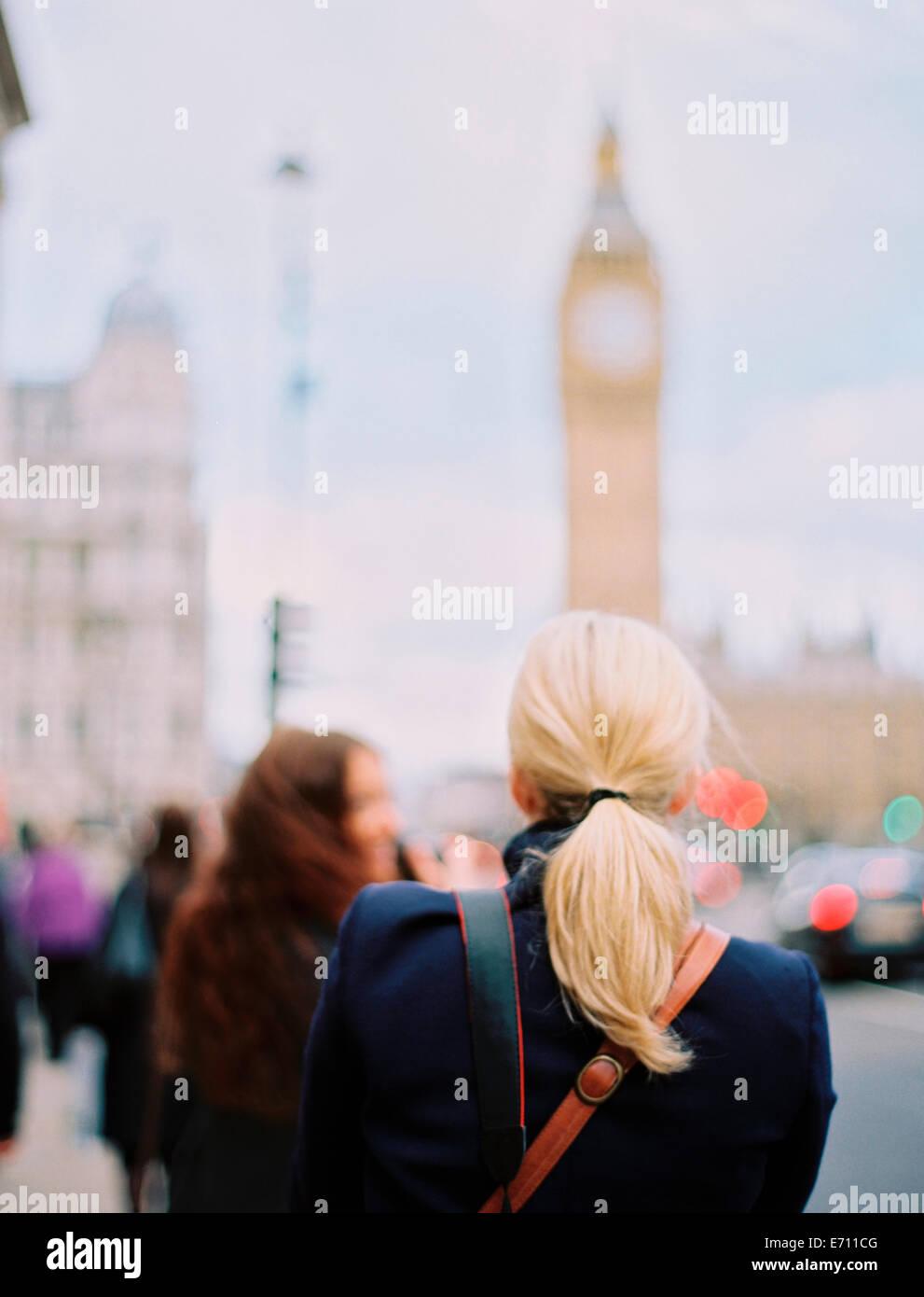 Two women in London on the street near Big Ben, The Elizabeth Tower in Westminster, in London. - Stock Image