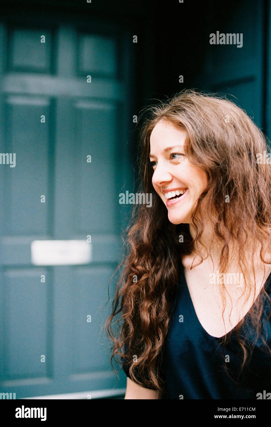 A woman smiling standing at an open doorway. - Stock Image