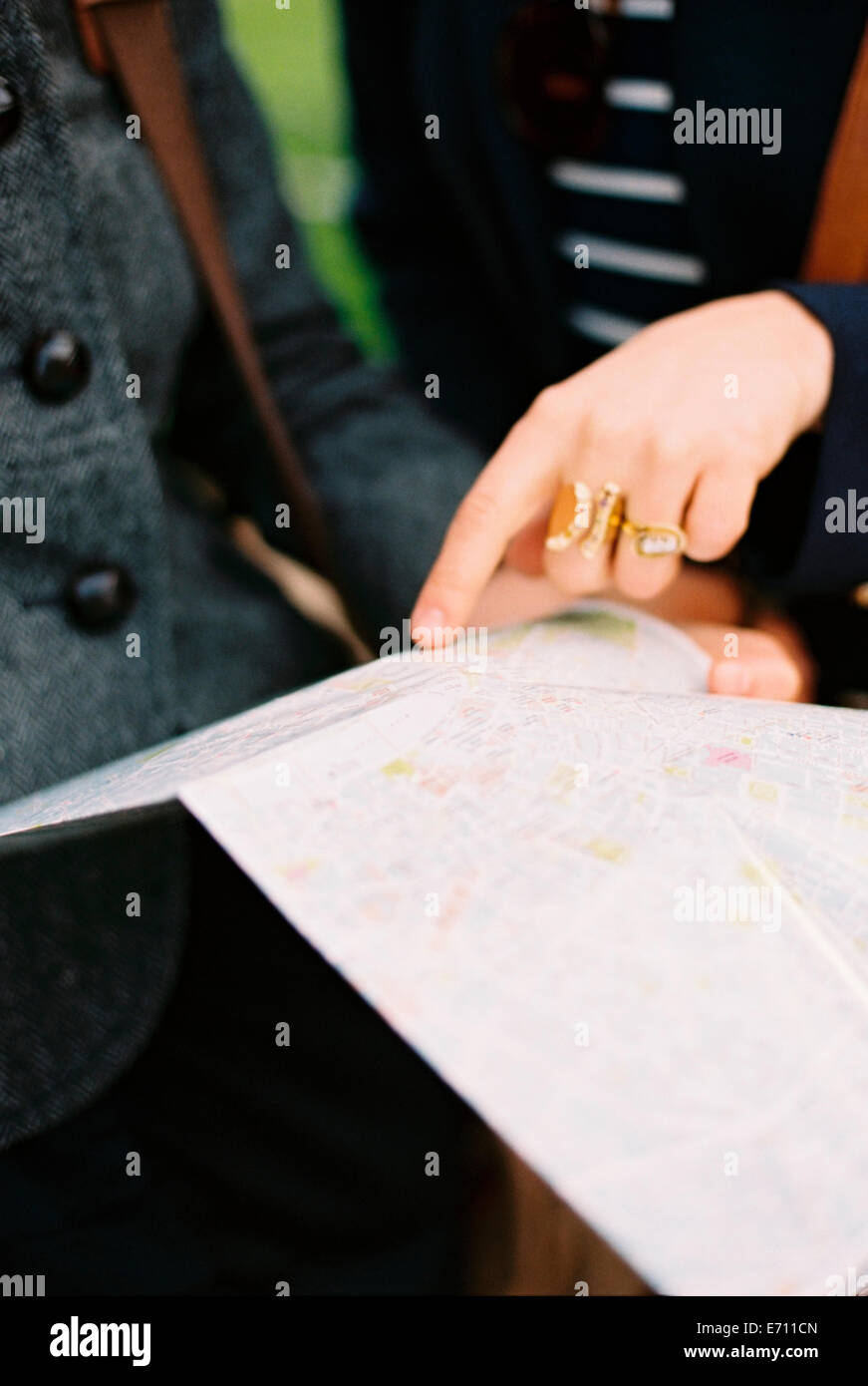 Two people using a map or guide book to find their way around a city. - Stock Image
