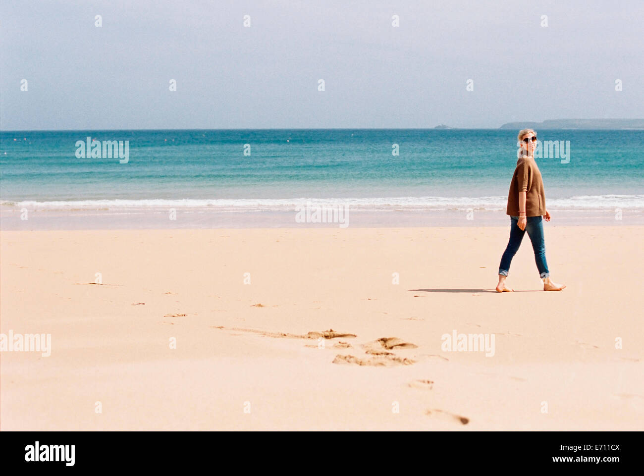 A woman walking barefoot on a beach, leaving footprints in the sand. - Stock Image