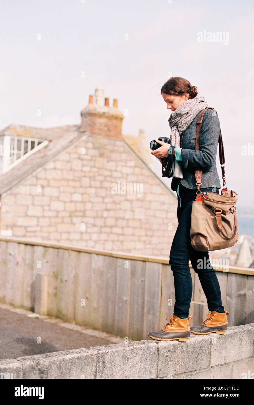 A woman with a large bag, holding a camera, standing on the top of a wall. - Stock Image