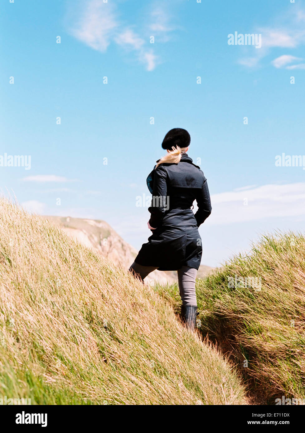 A woman in a coat and beret standing among the sand dunes by the coast. - Stock Image