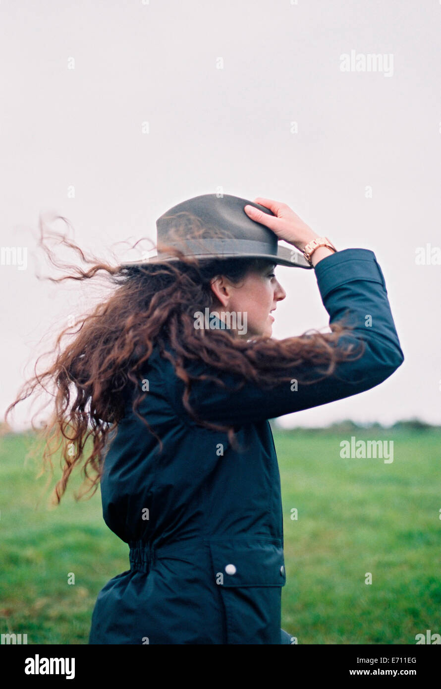 A woman with long hair being blown in the breeze, holding her hat. - Stock Image