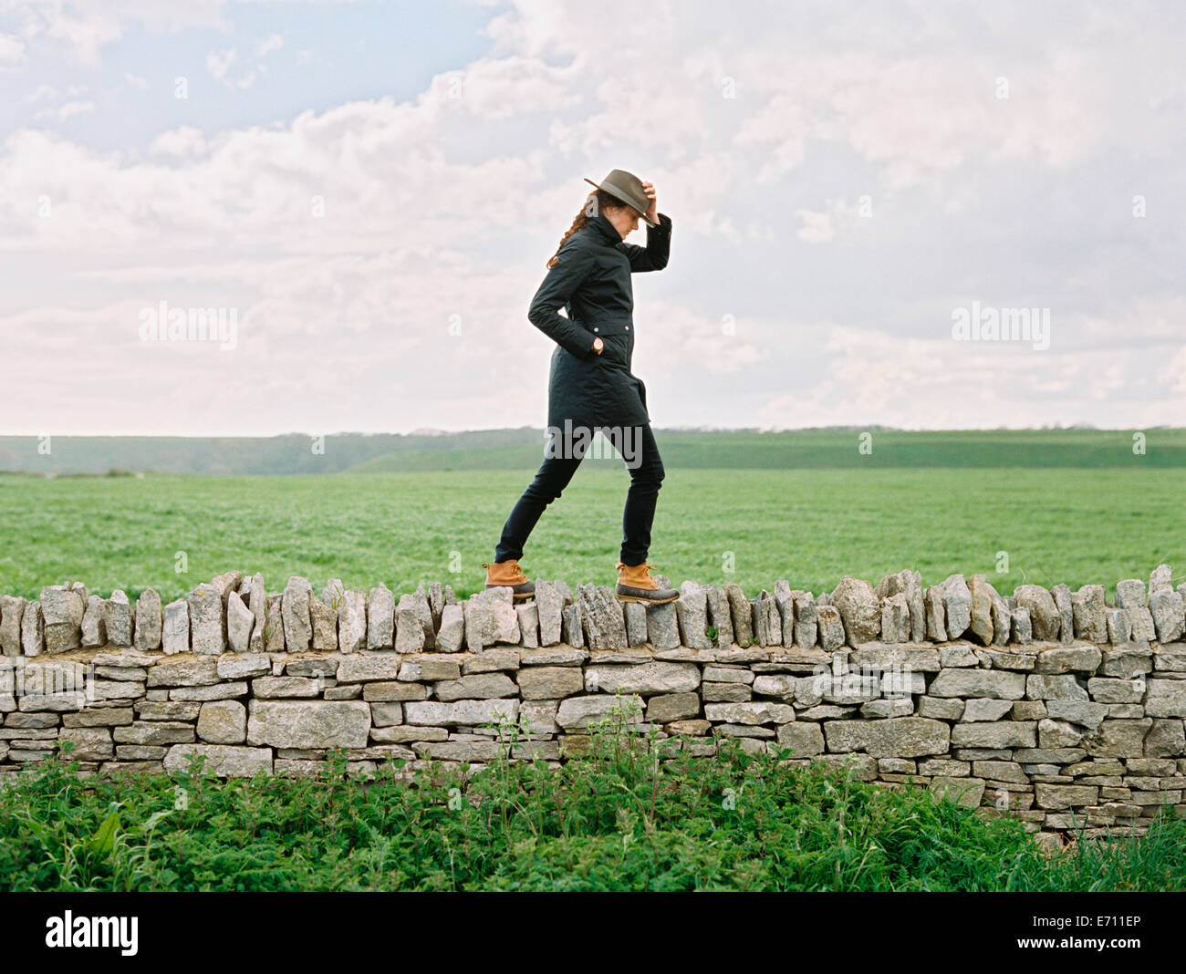 A woman in a hat walking along the top of a dry stone wall in a field. - Stock Image