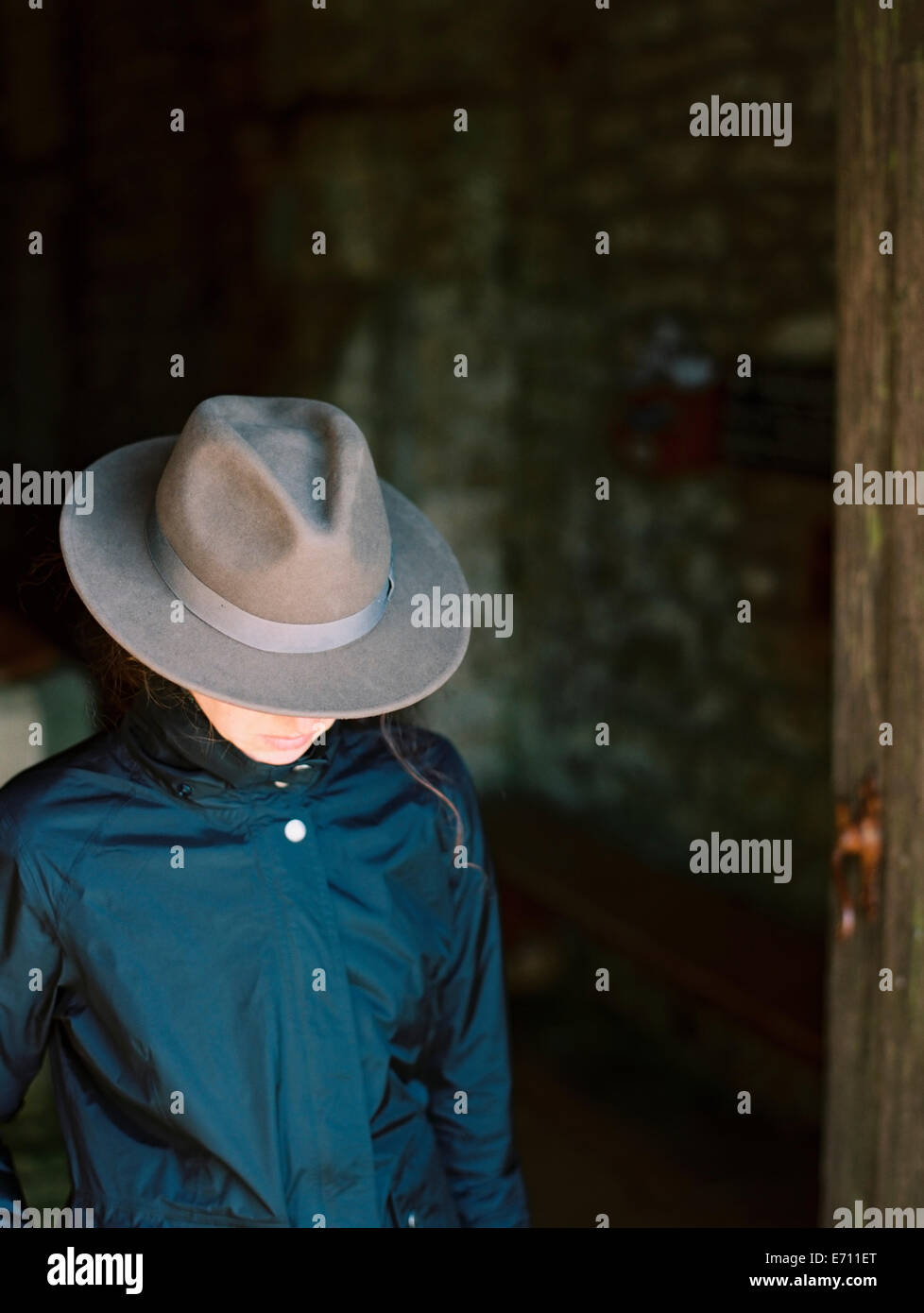 A woman with her face hidden by a hat with a brim. - Stock Image
