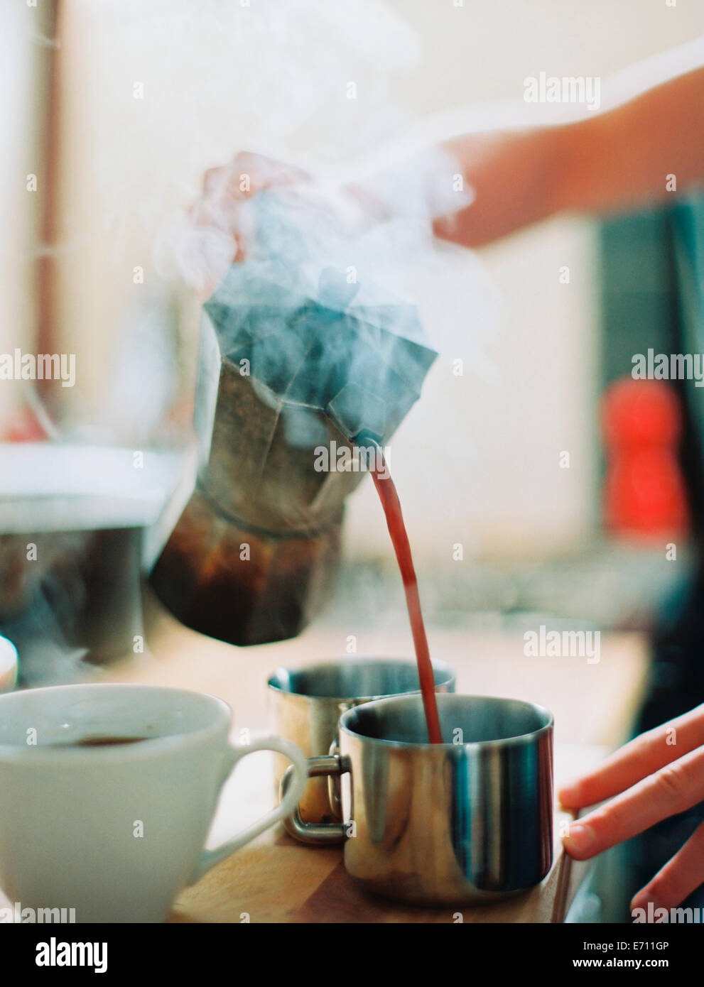 A person holding a coffee perculator and pouring hot coffee into cups. - Stock Image