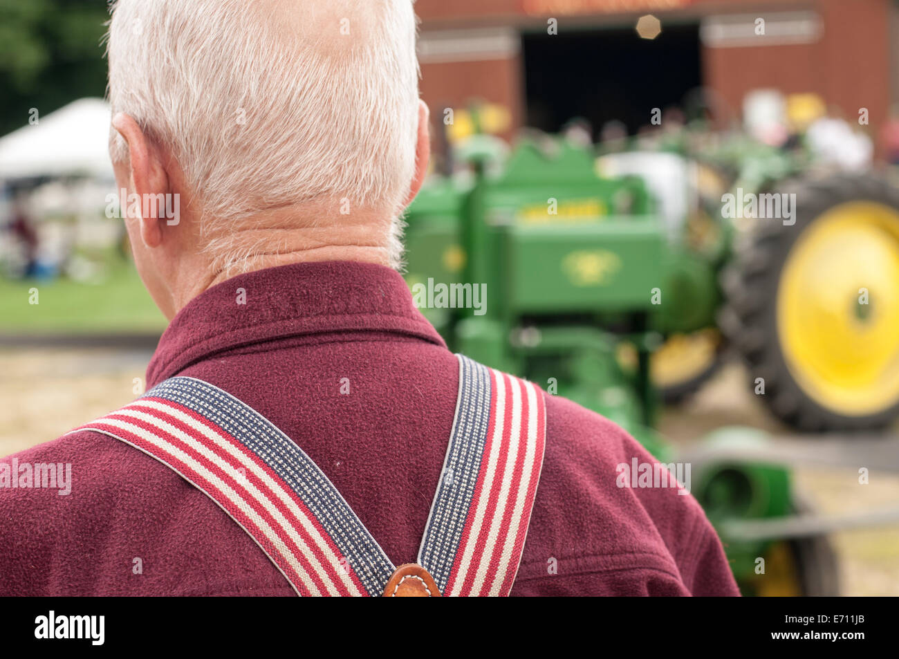 A farmer wearing American flag suspenders at a John Deere tractor expo in New Boston, New Hampshire, USA. - Stock Image