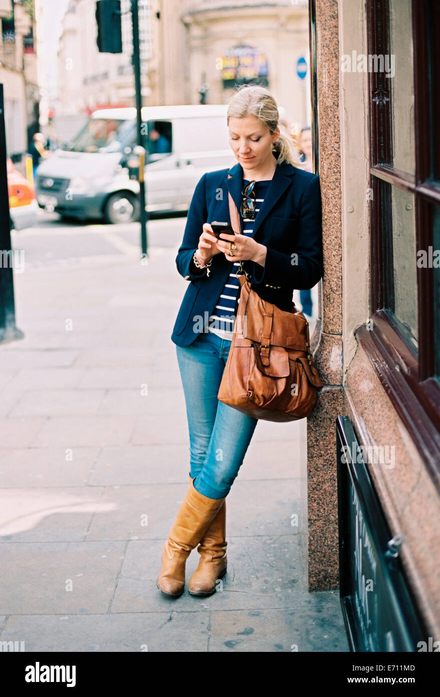 A woman checking her phone leaning against a wall on the street. - Stock Image