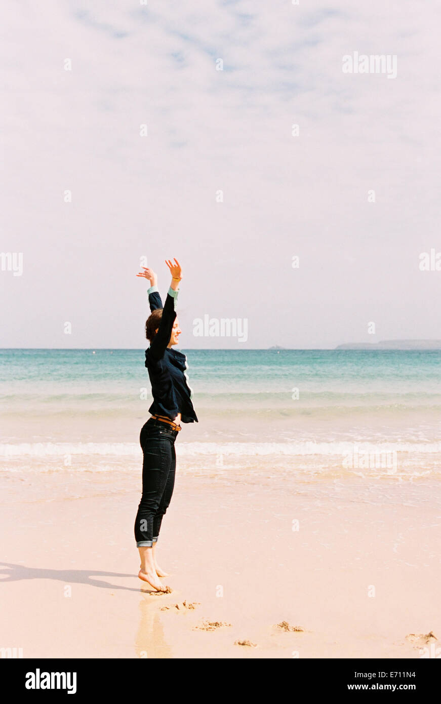 A woman standing barefoot on the sand raising her arms above her head, in a gesture. - Stock Image