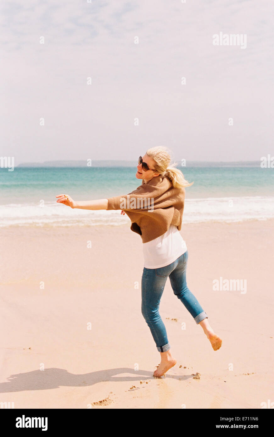 A woman dancing barefoot on the sand, expressing herself through movements. - Stock Image