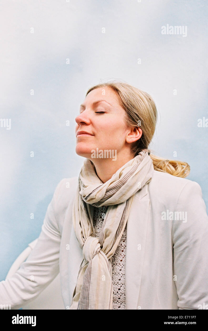 A woman with blonde hair sitting with her eyes closed and her head tilted back, feeling the sun on her face. - Stock Image