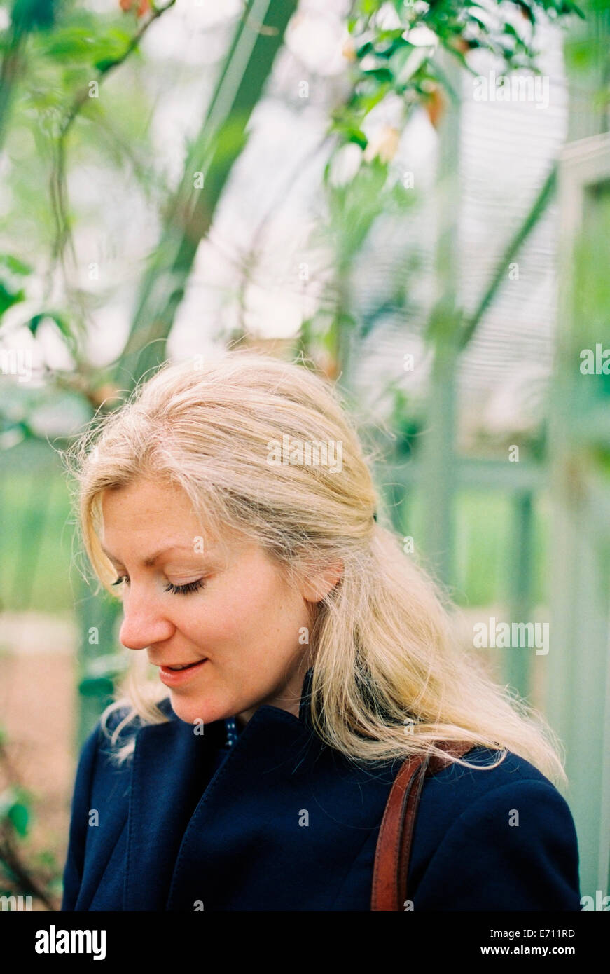 A blonde haired woman in a conservatory or tropical plant house. - Stock Image