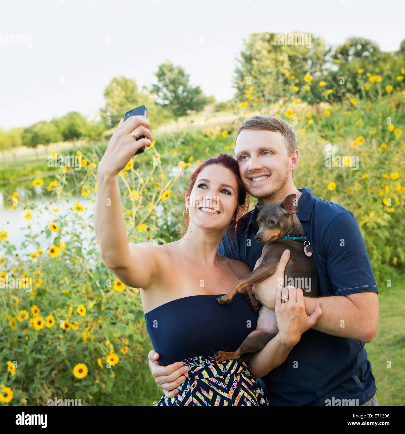 A couple playing with their small dog in the park, taking a selfy. - Stock Image