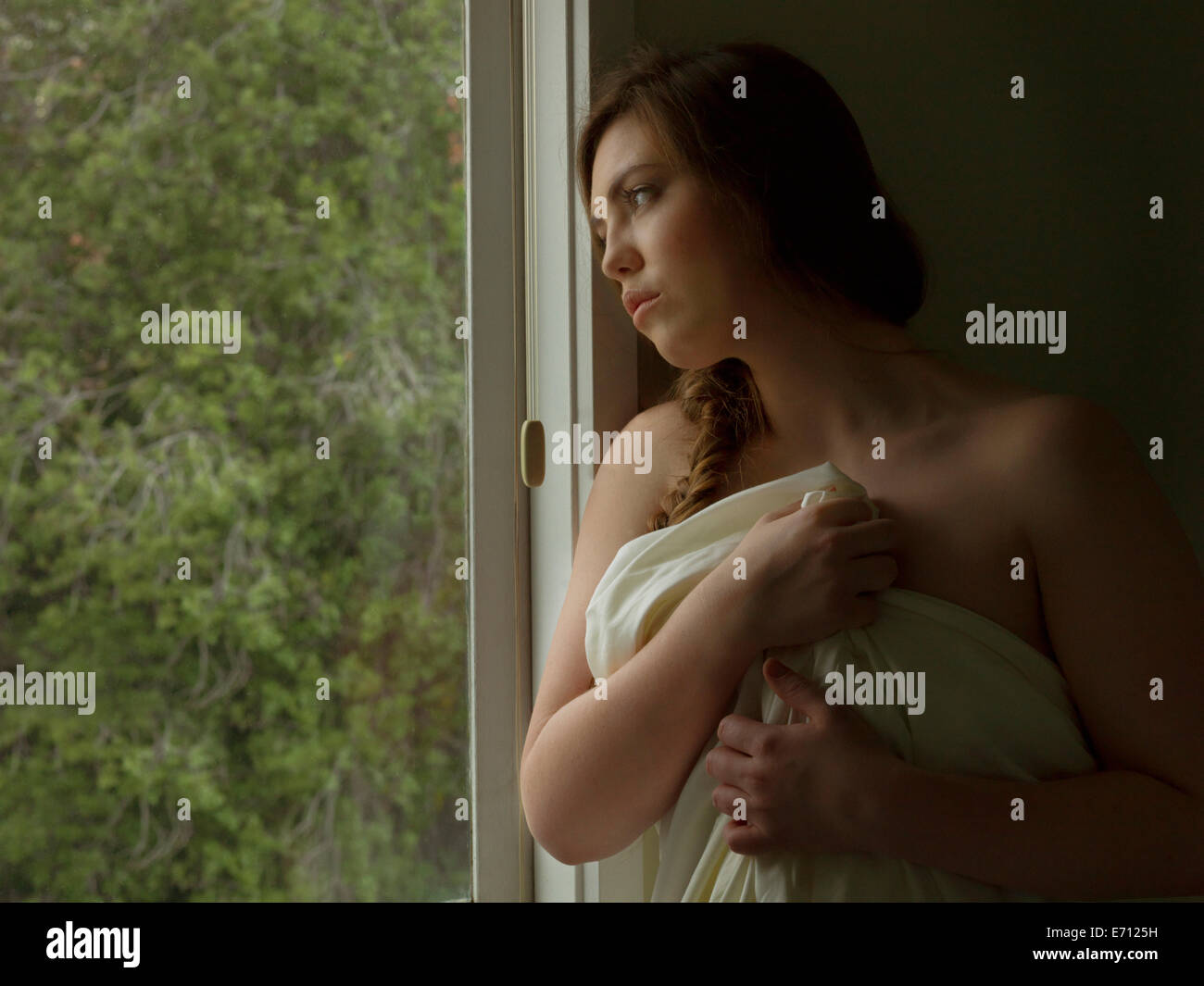 Sad young woman gazing out of hotel bedroom window whilst wrapped in sheet Stock Photo