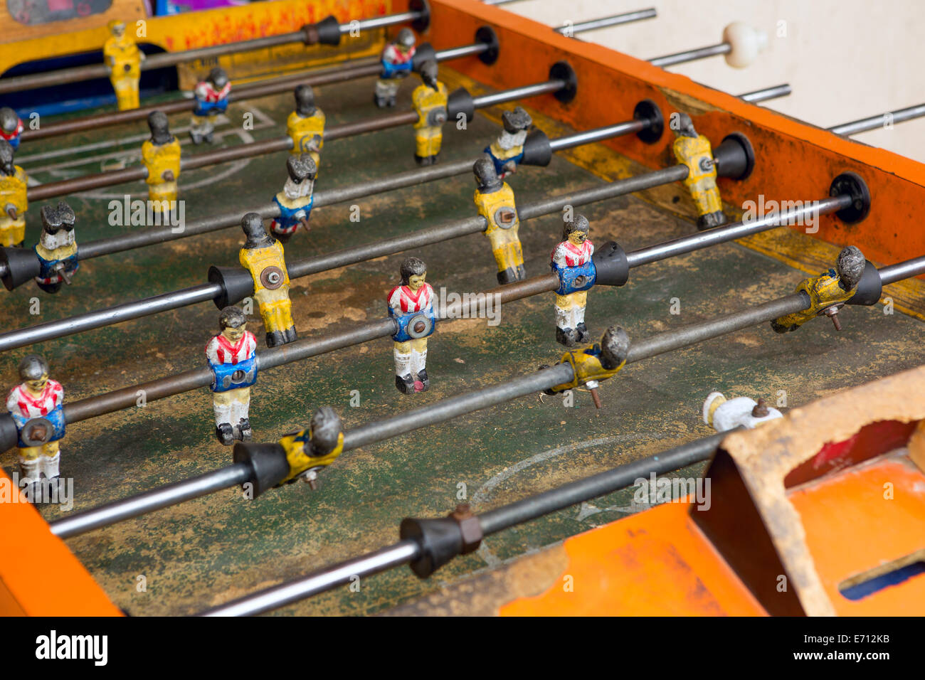Old fussball table detail with colorful players - Stock Image