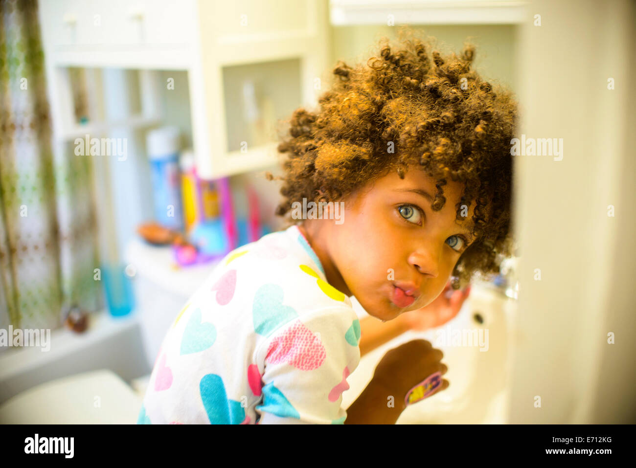 Portrait of girl rinsing mouth in bathroom - Stock Image
