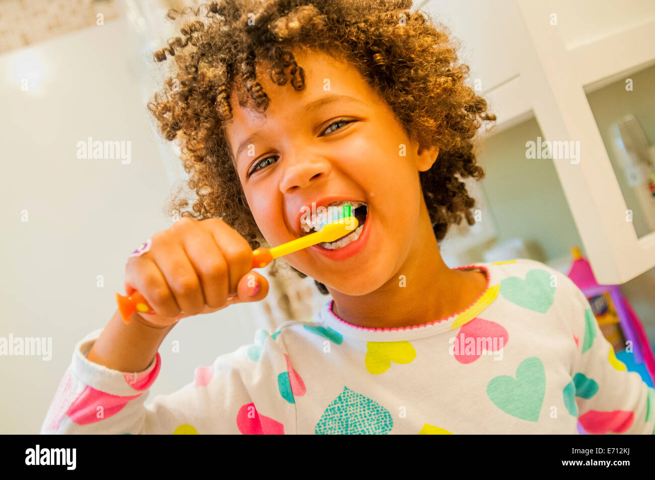 Portrait of smiling girl brushing teeth in bathroom - Stock Image