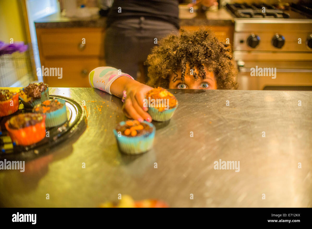 Portrait of girl reaching for cupcakes at kitchen counter - Stock Image